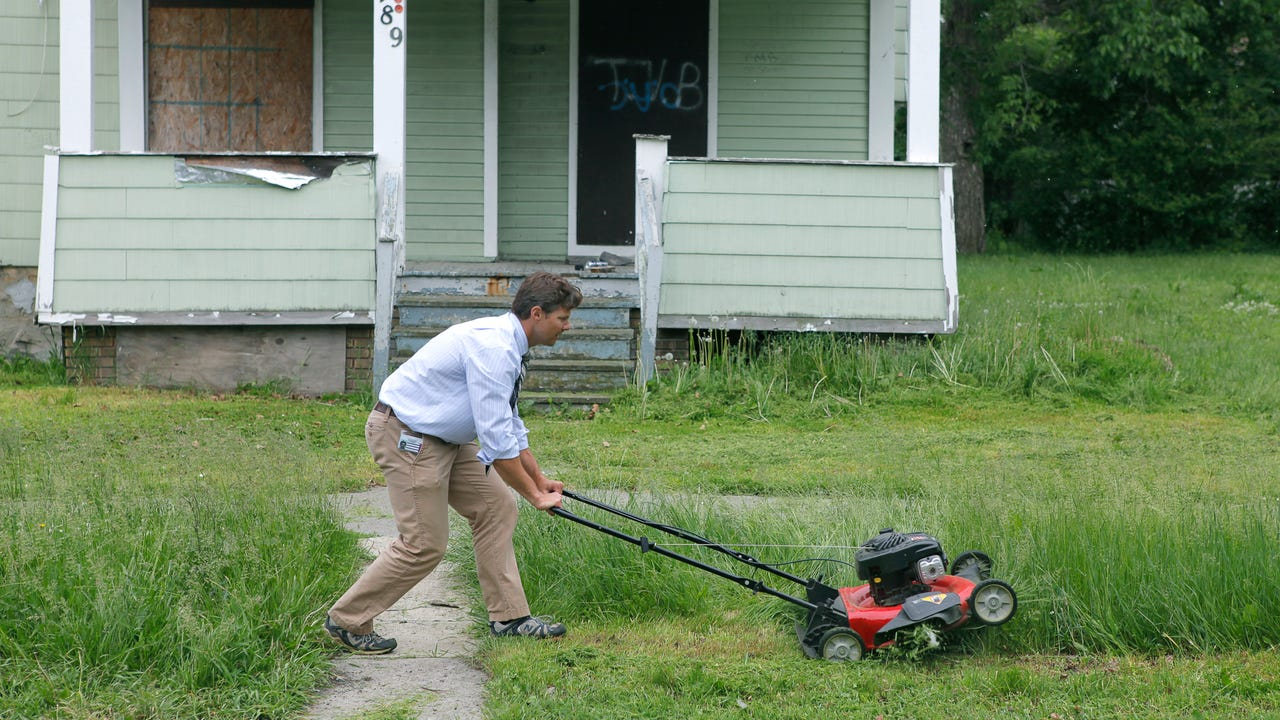 Democrat and Chronicle columnist Dave Andreatta mows the front lawn of a house at 489 Central Park that used to be owned by State Assemblyman Dave Gantt and now belongs to the city in Rochester, N.Y. on Thursday June 5 2014. Carlos Ortiz.