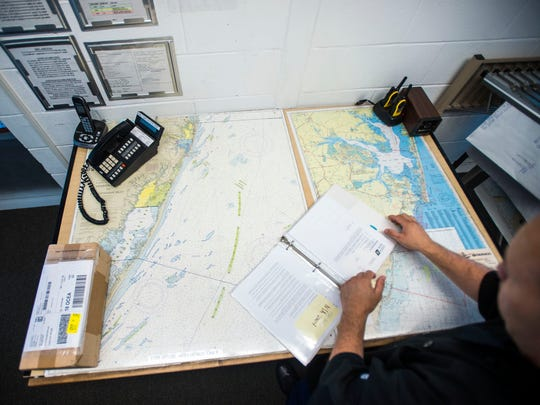 Petty Officer 3rd Class E4 Thomas Dagle prepares documents in the main office of the United States Coast Guard Station in Ocean City. The Coast Guard's real workplace is out on the open water, in an area of responsibility stretching from the Delaware state line to Chincoteague Bay.