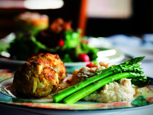 Jumbo lump crab cakes at Parkway are served over a sweet chili remoulade with smashed red potatoes and fresh asparagus.