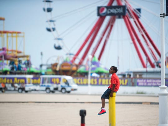 A young boy checks out the scene from atop a post on a mild  afternoon on the Ocean City Boardwalk.