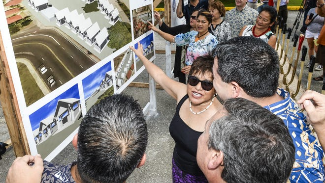 Legislative Speaker Judith Won Pat, facing with sunglasses, and other government officials look at conceptual drawings of permanent huts during a groundbreaking ceremony near the Chamorro Village in Hagatna on Thursday, Nov. 12. The ceremony was held to begin construction of a village consisting of 32 huts planned to be used during the 12th Festival of the Pacific Arts, to be hosted by Guam from May 22, through June 4, 2016. The festival coordinating committee approved the sum of $1.9 million to be used for the construction of the buildings, said Robert Lizama, FestPac committee member.