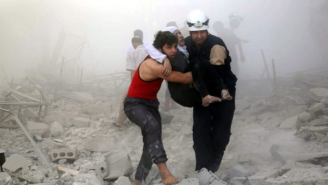An undated handout picture made available by the Syria Civil Defence volunteer organization on October 7, 2016, showing volunteers carrying a female victim in Syria.