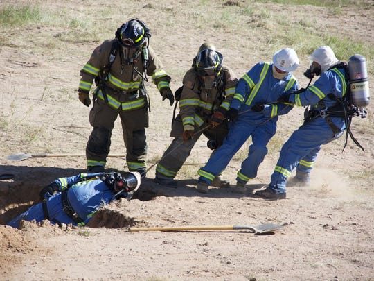 "PHOTO 2: During the gas leak training, one the LCU workers ""collapses"" into a hole and is ""rescued"" by the Las Cruces Fire Department."