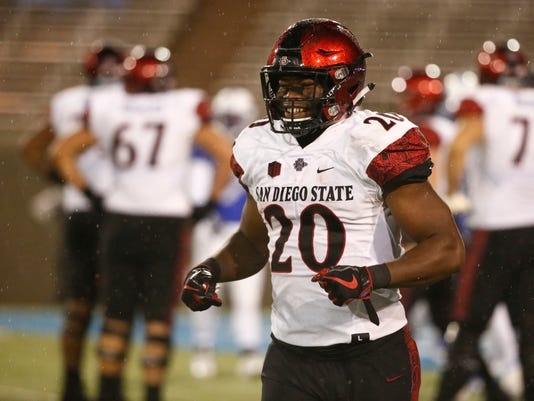 San Diego State running back Rashaad Penny (20) smiles as he heads back to the bench after scoring a touchdown against Air Force during an NCAA college football game, Saturday, Sept. 23, 2017, at Air Force Academy, Colo. (AP Photo/Jack Dempsey)