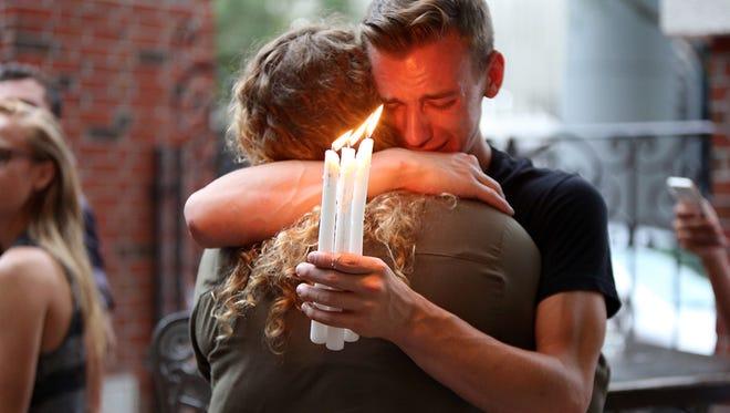 Brett Morian, from Daytona Beach, hugs an attendee during the candlelight vigil at Ember in Orlando, Fla., on Sunday, June 12, 2016.
