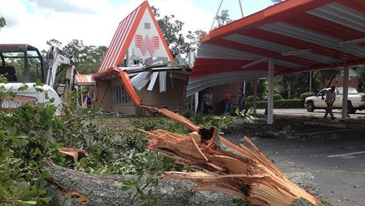 "A clean-up crew from Milton works to clear an oak tree that smashed the ""Historic"" Whataburger in Midtown."