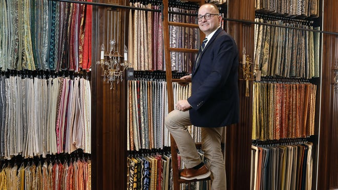 Benjamin Peterson, the owner of B. Peterson Palm Beach, stands on ladder next to a wide assortment of Fortuny textiles.