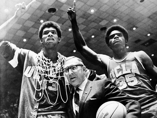 FILE - In this March 24, 1969, file photo, UCLA coach John Wooden is flanked by Sidney Wicks, right, and Lew Alcindor, draped with basket ropes, after the UCLA team beat Purdue 92-72 to win the NCAA basketball title for the third consecutive year, in Louisville, Ky.  (AP Photo, File)