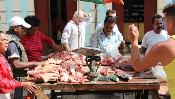 Cubans buy and sell goods at a farmers market in Parque