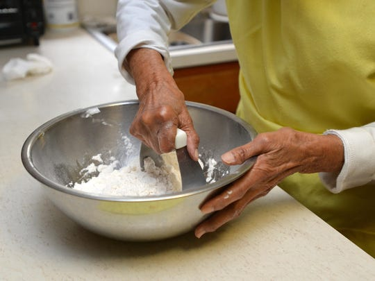 Ardella Ballard, 98, of Dublin, Md., cuts the dry ingredients until they form small balls before adding the sweet potato.