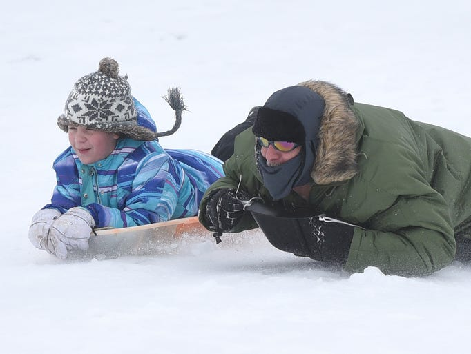 Mike Wilson, of Warren, enjoys sledding down a slope