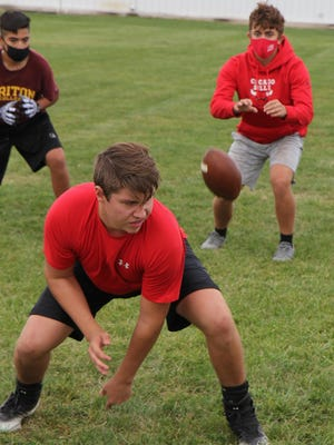United quarterback A.J. Jenks takes a snap from Devin Bushong on Thursday, Oct. 1 during one of the Red Storm's football contact days.