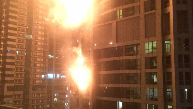 Flames rise from a high rise tower in Dubai's marina district on Saturday, Feb. 21, 2015.
