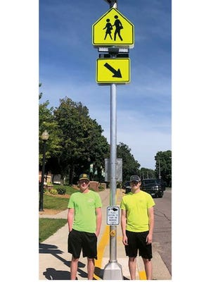 Dallas Bauer (left) and Kyle Tauer, 2019 graduates of St. Mary's High School, posed by the solar-powered pedestrian crossing sign by the school.  The sign is the result of their spring 2019 Environmental Science class project. Dallas and Kyle graduated before experiencing the benefit of their project, but were happy to see it installed at last.
