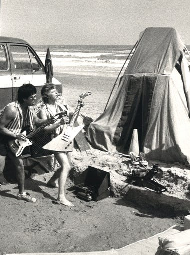 Texas Tech students Todd Gay (left) and Matt Montamat (right) (with guitars) entertained fellow beachgoers during spring break from the pit they dig for their performance March 11, 1984. They rigged up a generator so they could jam on their electric guitars.