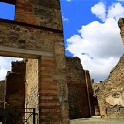 The sun shines on ruined walls in Pompeii, near modern-day