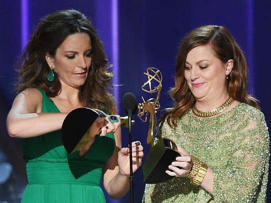 Actresses Tina Fey (L) and Amy Poehler speak onstage