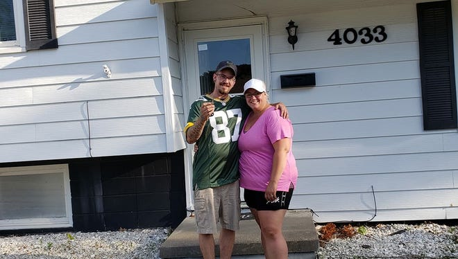 Shane and Christina Rhoades stand outside of their new home in Urbandale. Their previous condominium exploded, due to heavy flash flooding that devastated the Des Moines-area.