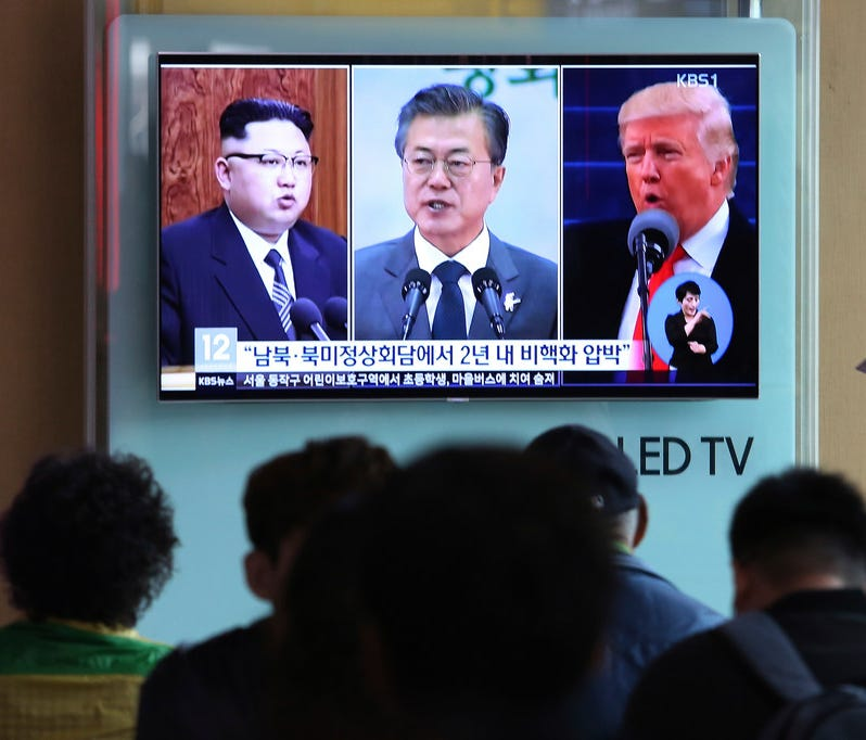 People watch a TV screen showing file footage of President Trump, right, South Korean President Moon Jae-in and North Korean leader Kim Jong Un, left, in Seoul, South Korea, on April 18.