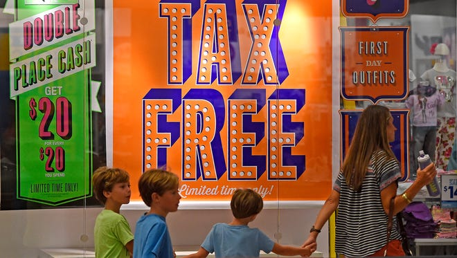 Customers pass by signs at Opry Mills advertising Tax-Free weekend sales during the TN sales tax holiday July 29-31.  Friday July 29, 2016, in Nashville, Tenn.