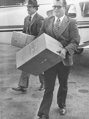 Former Abilene Christian University coach Wally Bullington, right, unloads footballs off a plane in preparation for an NAIA Division I playoff game.
