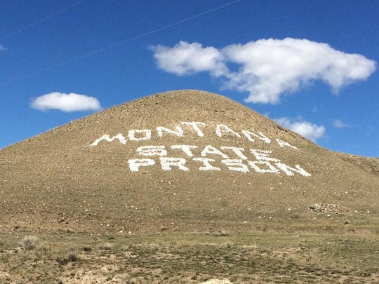 Stones spell out Montana State Prison on a hill outside the entrance of the facility in Deer Lodge.