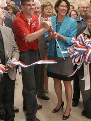 Steve Koponen, Class of '89, and Superintendent Michele Harmala help cut the ceremonial ribbon. Koponen, a Farmington Hills resident who teaches in Farmington schools, was instrumental in raising funds.