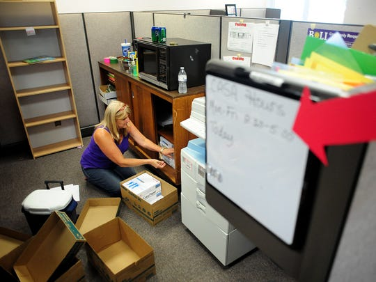 CASA volunteer Lori Hartman packs items into boxes as they move out of the Department of Human Services building Friday.