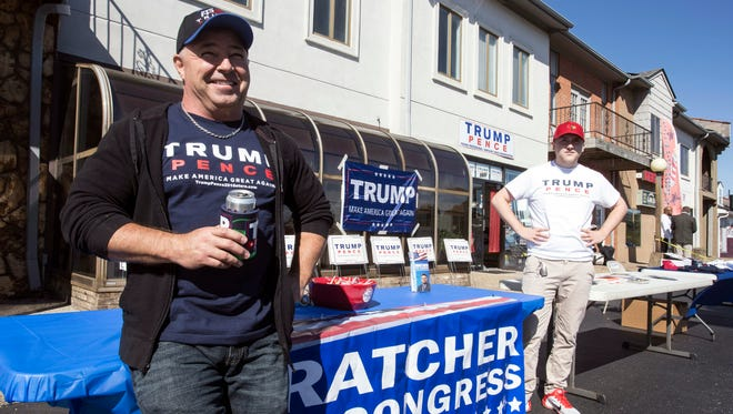 Trump supporters Jeff Klusmeier and Evan Wright man the merchandise tables at a rally in Fern Creek for the Republican candidate for president on Oct. 24.