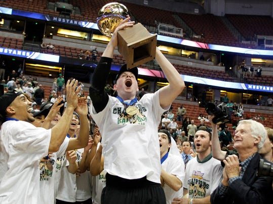 Cal Poly forward Zach Gordon, center, catches the trophy thrown to him from the head coach, Joe Callero, in celebration of defeating Cal State Northridge 61-59 in the NCAA Big West tournament championship college basketball game in Anaheim, Calif., Saturday, March 15, 2014. (AP Photo/Alex Gallardo)