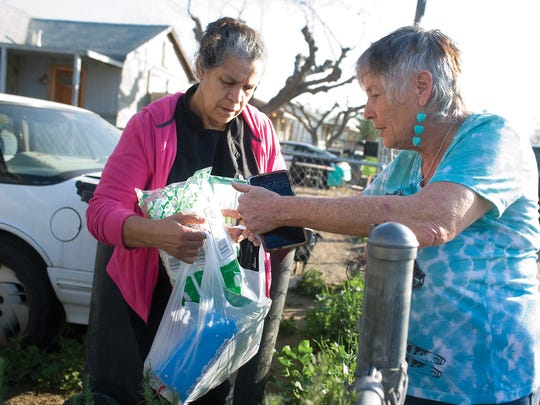 Donna Johnson, right, hands out plastic silverware and paper plates as she delivers bottles of water to Jane Tapia, left, on Jan. 30 in East Porterville.