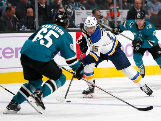 St. Louis Blues center Robby Fabbri (15) moves the puck down ice against San Jose Sharks defenseman Erik Karlsson (65) during the second period of an NHL hockey game in San Jose, Calif., Saturday, Nov. 17, 2018. (AP Photo/Tony Avelar)