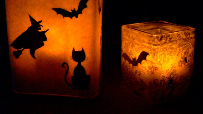 Attach black stickers to vellum or the waxy side of freezer paper and wrap around a clear glass vase, adhering with double-sided tape. Insert battery-operated votives and enjoy the trembling glow.