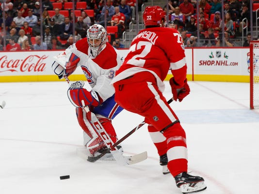 Montreal Canadiens goalie Carey Price (31) clears the puck from Detroit Red Wings left wing Andreas Athanasiou (72) in the second period of an NHL hockey game Thursday, Nov. 30, 2017, in Detroit. (AP Photo/Paul Sancya)