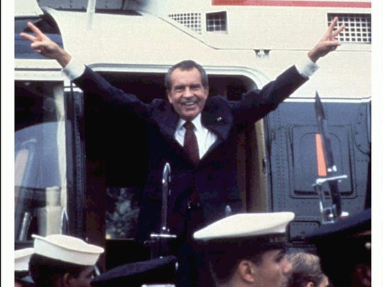 """Former president Richard Nixon is shown here giving his """"V"""" sign while boarding a helicopter following his resignation."""
