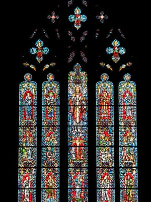 A radiant stained glass window inside of Heavenly Rest Episcopal Church features several saints.