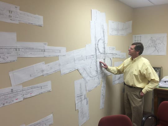 Richard Palmer, of the Delaware Department of Transportation, looks over the plans for the Del. 141-Interstate 95 interchange project. Work began in this month, causing long lines of traffic.