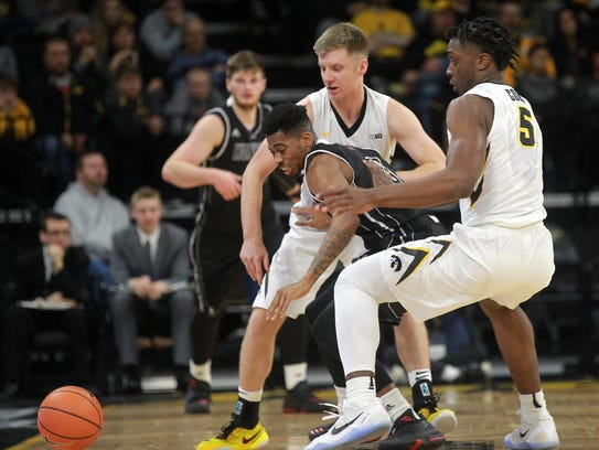 Iowa's Brady Ellingson and Tyler Cook (5) knock the