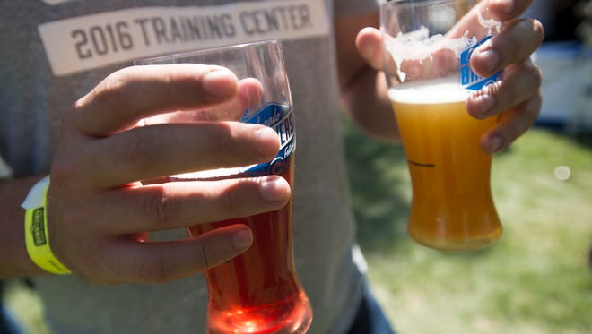 A festival attendee holds onto beer samples during the Colorado Brewers' Festival in Washington Park on Saturday, June 24, 2017.