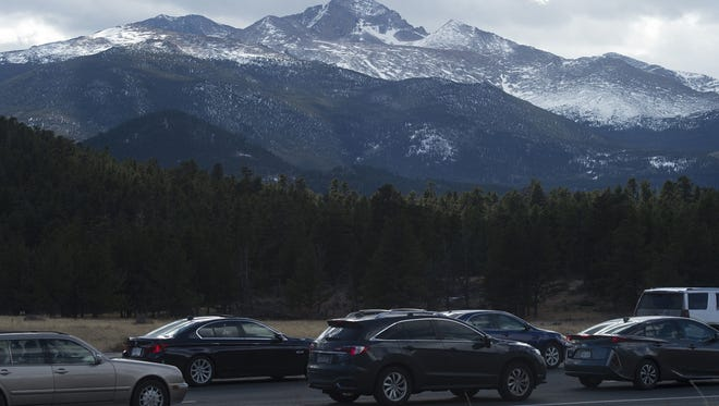 Longs Peak rises above a line of cars waiting at the Beaver Meadows entrance station to enter Rocky Mountain National Park in 2017.