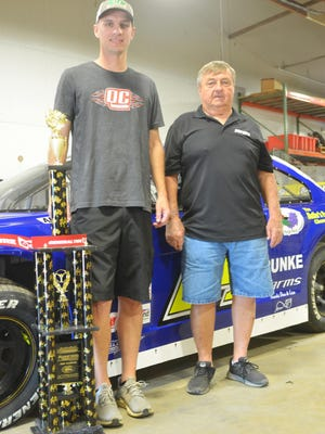 Ryan Unzicker (left) and Bill Hendren display the trophy they won in the 58th annual Allen Crowe Memorial race in Springfield, recently.