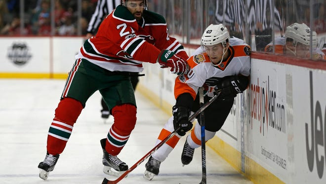 New Jersey Devils right wing Kyle Palmieri (21) checks Philadelphia Flyers center Jordan Weal (40) during the first period of an NHL hockey game, Thursday, March 16, 2017, in Newark, N.J. (AP Photo/Adam Hunger)