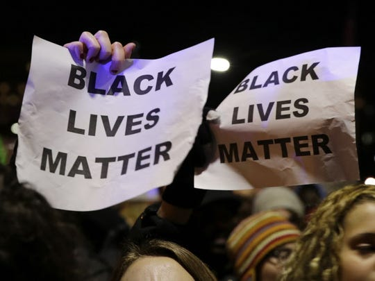 """Protesters in Boston hold up signs while chanting """"Black"""