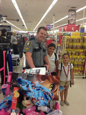 A Collier County sheriff's deputy poses with children amid their Kmart shopping spree. An anonymous donor with the Jewish Federation of Collier County gave $9,000.