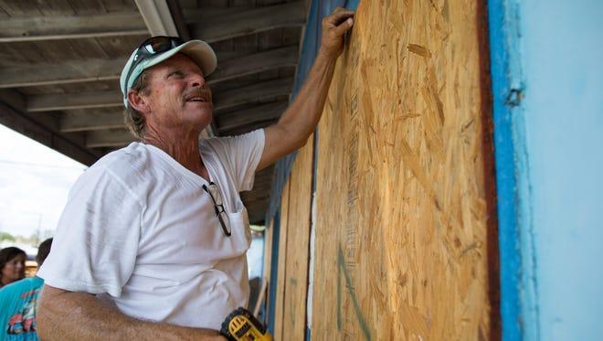 Mark Jones helps board up windows in Port Aransas ahead of hurricane Harvey on Aug. 24, 2017.