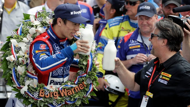 Indianapolis 500 winner Takuma Sato (left) celebrates with car owner Michael Andretti with a traditional bottle of milk.