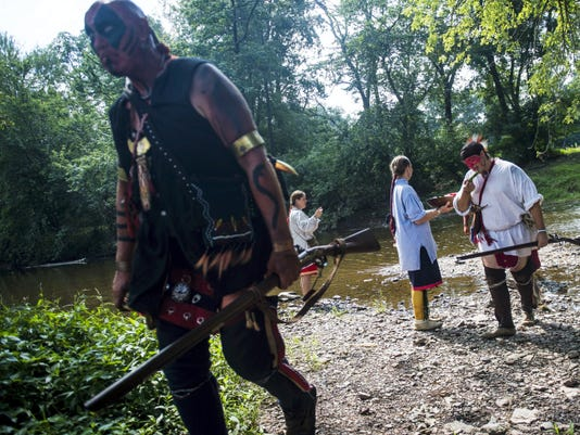 Re-enactors portraying Native Americans with the Shawnee tribe, Tom Hinkelman, of Mount Laurel, New Jersey, left, and Eric Beachy, of Chambersburg, middle, pick up some watermelon from re-enactor Elizabeth Huxford while crossing the creek after participating in a re-enactment of a skirmish between British and French and Shawnee forces during Mason and Dixon Day at the Mary-Penn Bed and Breakfast on Saturday near Gettysburg.