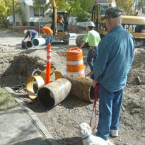 Ken Croscutt and Max watch the action as a crew from Ed Boland Construction lays a section of new water main on 23rd Street North in 2006.