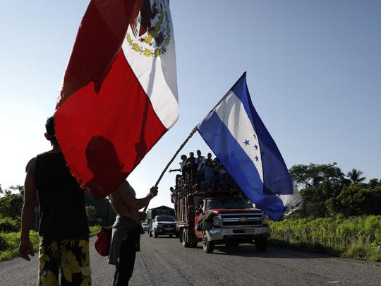 Honduran migrants walking north wave the flags of Honduras and Mexico to passing trucks.