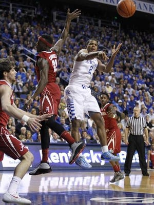 Aaron Harrison dishes to a teammate during the first half of Saturday's game against Alabama.